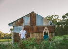 Engaged couple standing in front of rusty barn