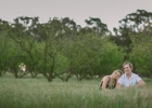 Engaged couple cuddling in meadow