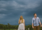 Engaged couple standing in front of storm clouds